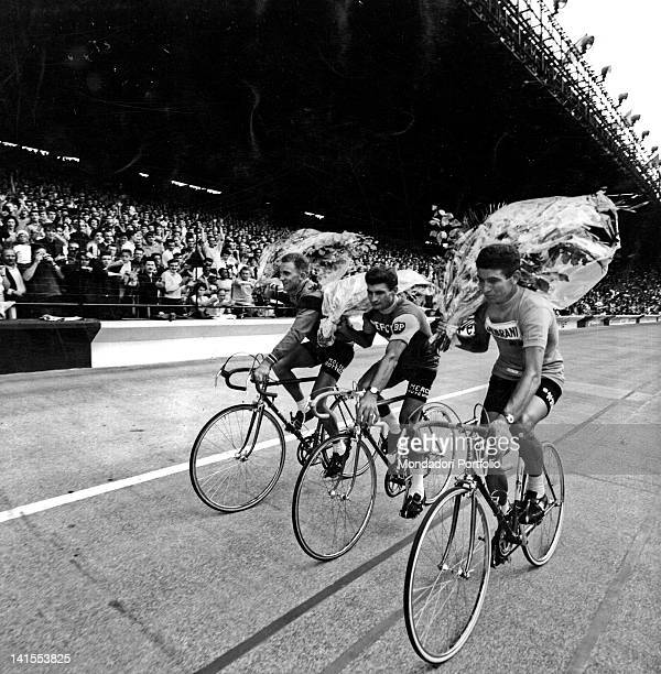 The racing cyclists Felice Gimondi Raymond Poulidor and Gianni Motta cycling the lap of honour after the award ceremony at Parc des Princes Paris...