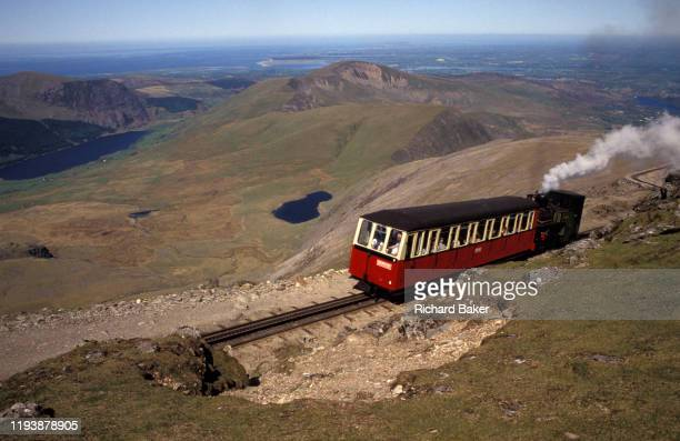The rack and pinion narrow guage mountain railway nearing the summit of Mount Snowdon, the highest point in England, on 14th June 1992, in Llanberis,...
