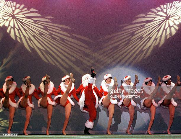 The Radio City Rockettes exhibit precision highkick cancan abilities while Santa tries to compete in a special show 06 December 1999 before hundreds...