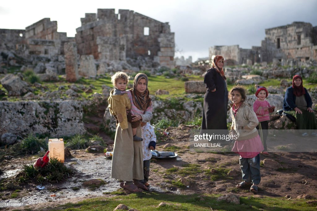 The Radwan family stand in front of an ancient building in the old Roman city of Serjilla, in northwestern Syria, where they set up their home in the ruins on February 11, 2013, after fleeing the fighting between rebel forces and pro-government troops in the town of Kfar Nubul, in the northwestern province of Idlib.