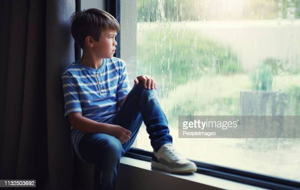 the rain washed away his fun for the day - one boy only stock pictures, royalty-free photos & images