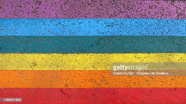 the rainbow of the lgbt community painted on a street in paris - orgulho imagens e fotografias de stock