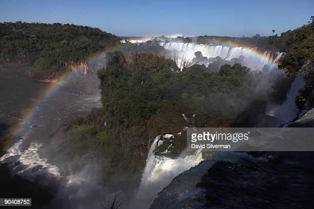 The rainbow which frames San Martin Island is formed by mist rising from the Iguacu Falls in the Iguazu National Park on August 13 2009 near the town...