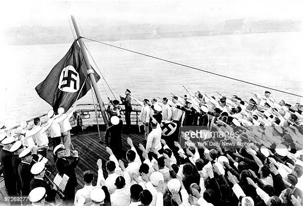 The raising of the new swastika flag aboard the SS Bremen docked in the Hudson River Captain Adolf Ahern behind the stand with the draped Nazi flag...