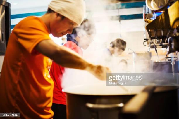 The ramen noodle shop. A chef stirring a huge pot of noodles cooking.