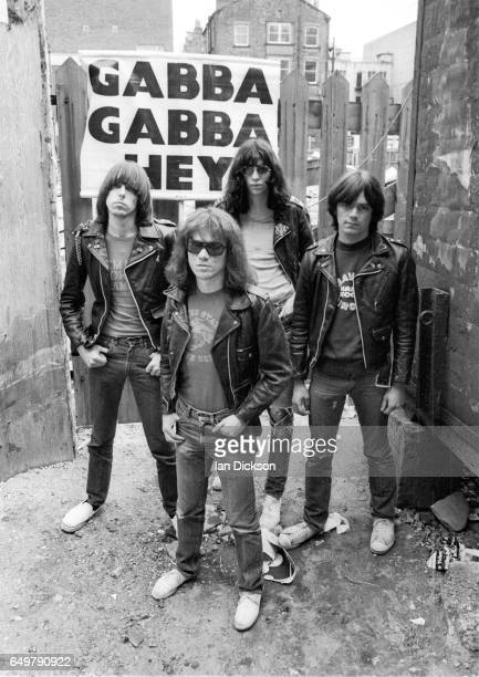 The Ramones pose for a group portrait with their 'Gabba Gabba Hey' placard near Eric's club, Liverpool, 19 May 1977. L-R Johnny Ramone, Tommy Ramone,...