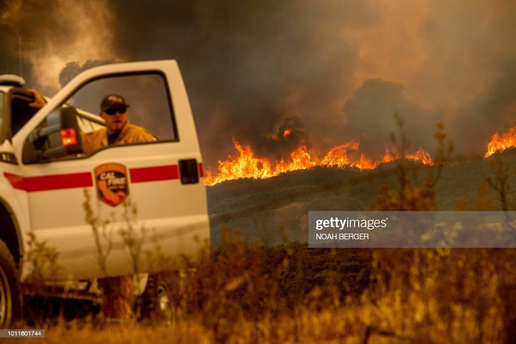 The Ranch Fire, part of the Mendocino Complex Fire, crests a ridge as Battalion Chief Matt Sully directs firefighting operations on High Valley Rd. near Clearlake Oaks, California, on Sunday, Aug. 5, 2018.