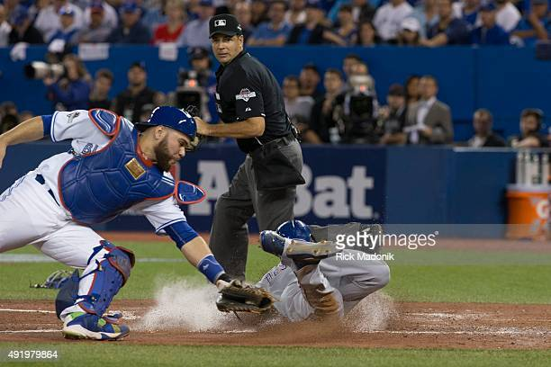 The Ranger's Delino DeShields slides past the tag of Jays catcher Russell Martin Toronto Blue Jays vs Texas Rangers in MLB playoff action at the...