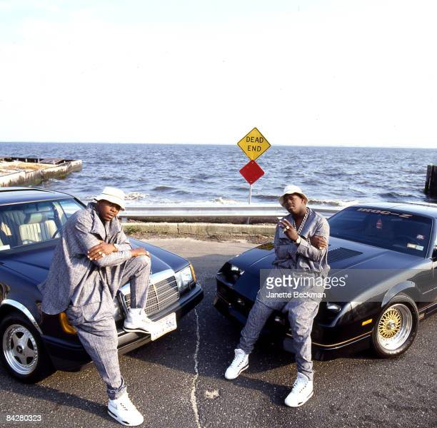 The rap group EPMD on left Parrish Smith or PMD and on right Erick Sermon or Eric Onassis lean on MercedesBenz and IROCZ Camaro automobiles...