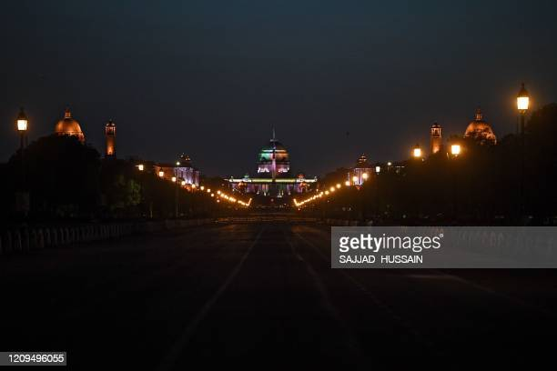 The Rashtrapati Bhavan is seen illuminated as seen from a deserted Rajpath during a government-imposed nationwide lockdown as a preventive measure...