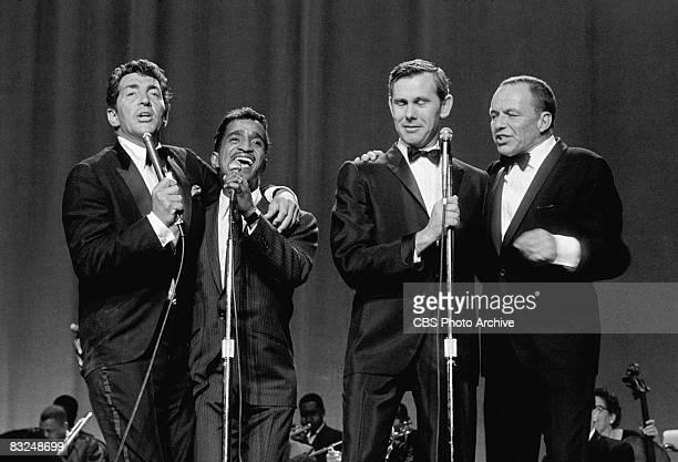 The Rat Pack Dean Martin Sammy Davis Jr and Frank Sinatra perform on stage with American television show host Johnny Carson as part of a benefit...