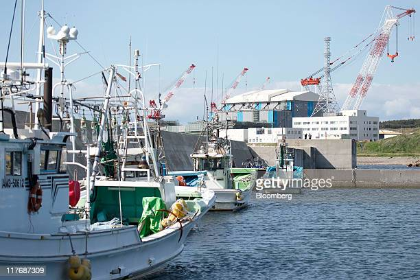 The reactor building for Electric Power Development Co's Oma nuclear power plant right stands under construction while fishing boats are moored at a...