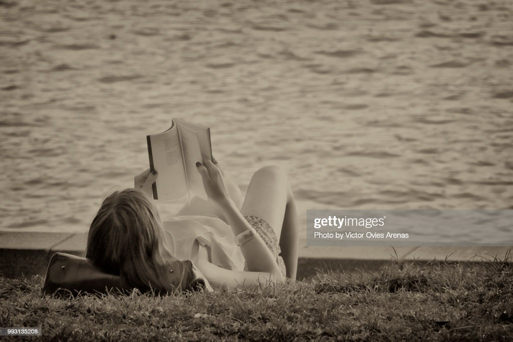 The reader: Woman reading a book by the pond in the Retiro Park in Madrid, Spai : Foto de stock