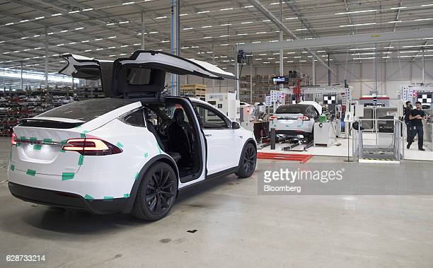 The rear gull wing doors of a Tesla Model X sports utility vehicle sit open during assembly for the European market at the Tesla Motors Inc factory...