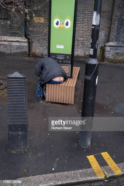The rear of a man is seen between clothing of a man bending down to listen to his phone that is re-charging at a Duolingo Wi-fi Smart Bench at...