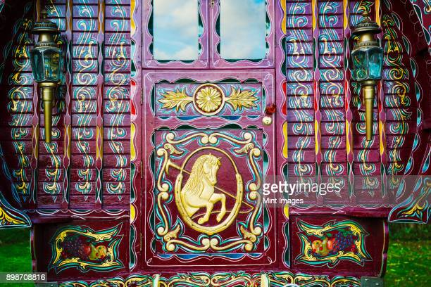 The rear of a traditionally decorated and painted gypsy caravan, door and windows.