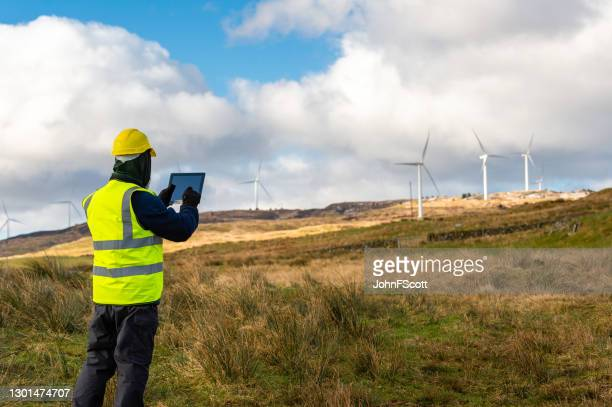 the rear view of a man using a digital tablet while out working in a remote location near a wind farm - remote location stock pictures, royalty-free photos & images
