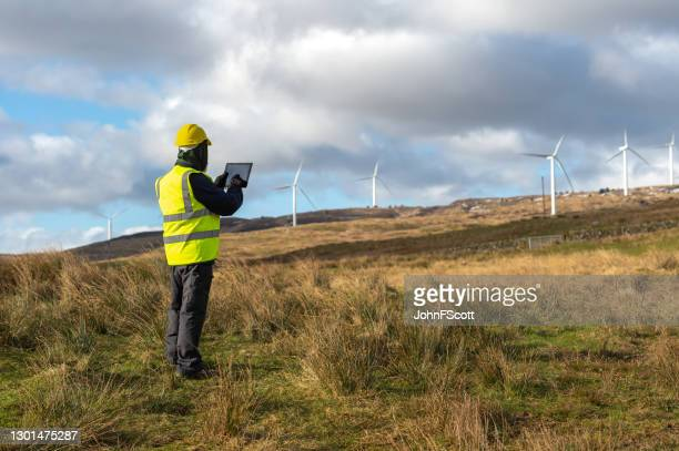 the rear view of a man using a digital tablet while out working in the field near wind turbines - johnfscott stock pictures, royalty-free photos & images