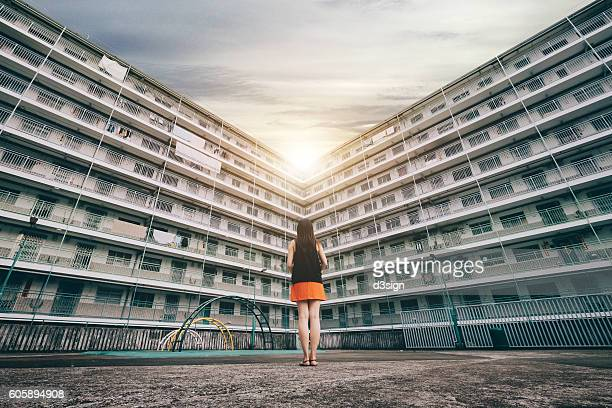 The rear view of woman standing against old apartment building, looking towards the sun shining