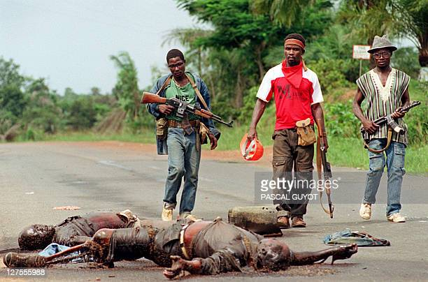 The rebels loyal to the warlord Charles Taylor holding Kalashnikov machine guns passes by a bodies of the soldiers loyal to the president Samuel Doe...