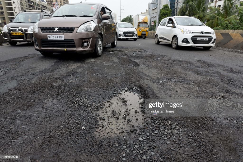 The recent heavy spell of showers has increased the problem of commuters as huge potholes have appeared on various roads in the city after rain, on July 11, 2018 in Mumbai, India. Heavy rains made a comeback in Mumbai causing waterlogging in many parts of the city leading to disruptions in traffic services and affected local train services. The India Meteorological Departments (IMD) Mumbai office has said heavy rainfall will continue in some parts of the city and its suburbs after similar conditions over the weekend.