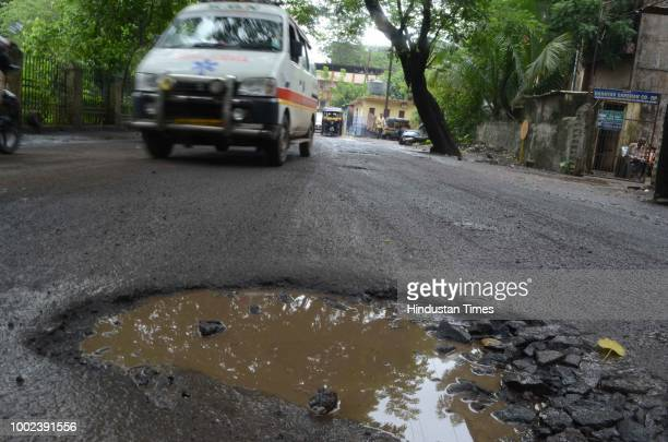 Municipal Corporation workers repairing potholes outside Commissioner Of Police Office Crawford Market on July 16 in Mumbai India
