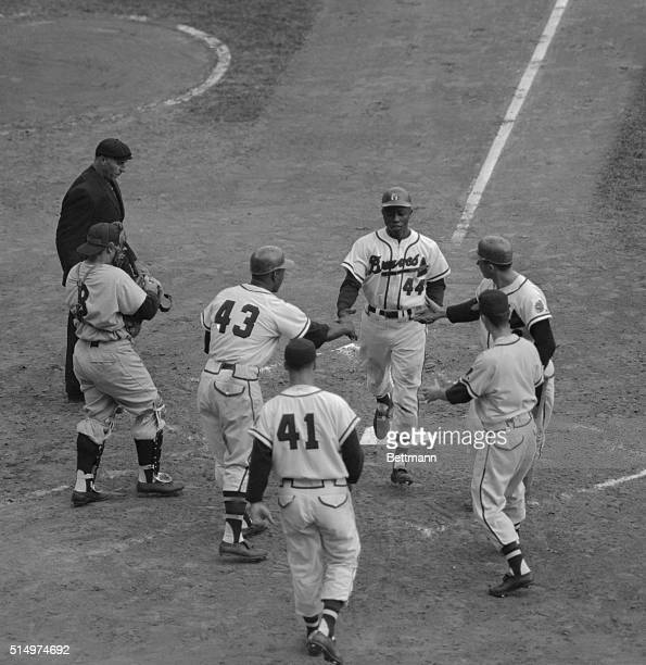 The reception committee is on hand as Hank Aaron toes home after belting a three run homer for the Milwaukee Braves in the fourth inning of the...