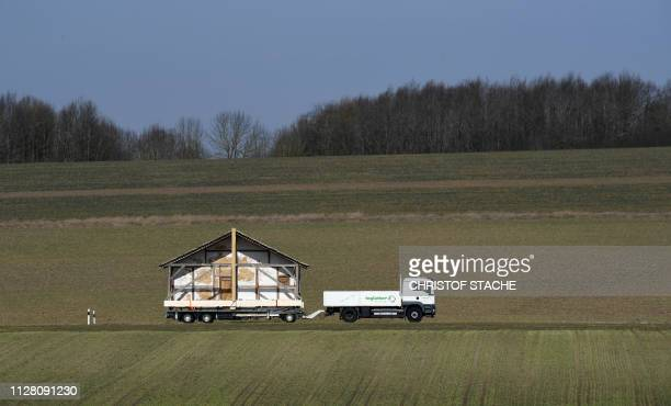 The reconstructed facade of an historic Roman house is being transported by a special transport on a street near the village of Wassertruedingen near...