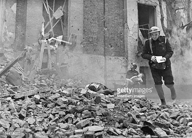 The Reconstruction Of 'An Incident' Civil Defence Training In Fulham London An Air Raid Warden runs across a large pile of rubble past a casualty...