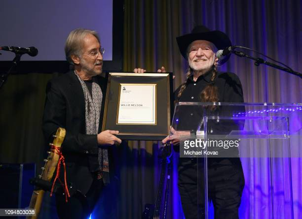 The Recording Academy and MusiCares President/CEO Neil Portnow honors Willie Nelson onstage during the Producers Engineers Wing 12th annual GRAMMY...