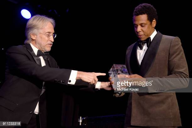 The Recording Academy and MusiCares President/CEO Neil Portnow presents the President's Merit Award to honoree JayZ onstage at the Clive Davis and...