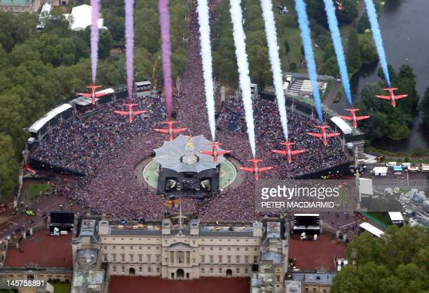 The Red Arrows fly over fly in formation over Buckingham Palace and huge crowds on the Mall to celebrate the Queen's Diamond Jubilee in London on...