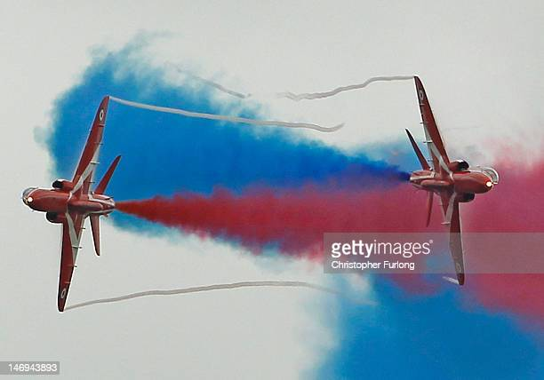 The Red Arrows leave red and blue smoke trails as they practise their 2012 air display at RAF Scampton on June 22 2012 in Scampton England The famous...