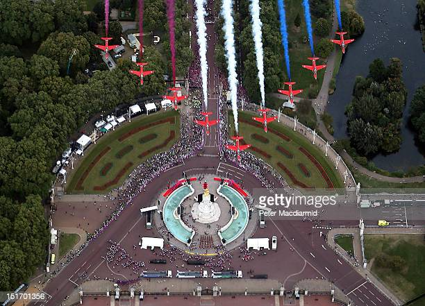 The Red Arrows Royal Air Force Aerobatic Team fly in formation over the Queen Victoria Memorial next to Buckingham Palace during the London 2012...
