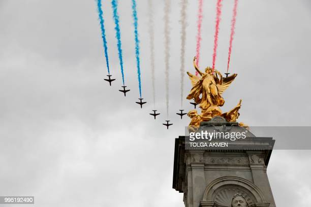 The Red Arrows take part in a flypast over the Queen Victoria Memorial on the Mall outside Buckingham Palace in London on July 10 2018 to mark the...