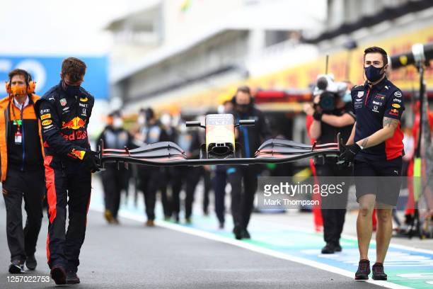 The Red Bull Racing team bring a new front wing after Max Verstappen of Netherlands and Red Bull Racing crashed on the way to the grid before the...