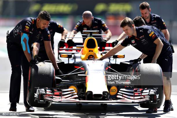 The Red Bull Racing team wheel the car of Daniel Ricciardo of Australia and Red Bull Racing down the pit lane during final practice for the Formula...