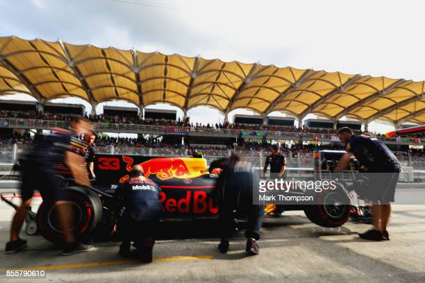 The Red Bull Racing team work on the car of Max Verstappen of Netherlands and Red Bull Racing in the Pitlane during qualifying for the Malaysia...