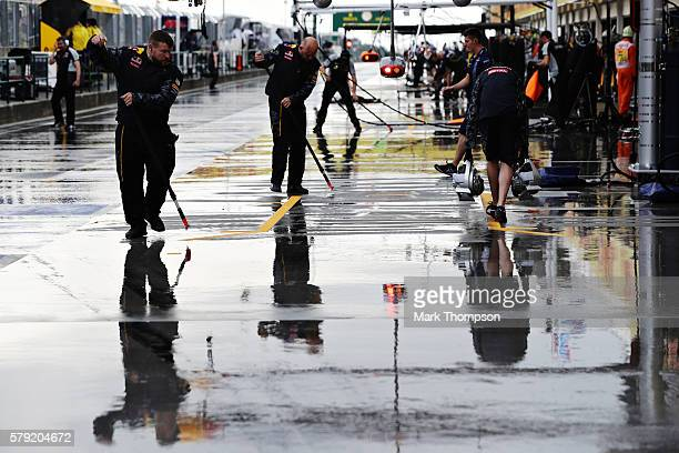 The Red Bull Racing team work to clear the rain from the pit box during qualifying for the Formula One Grand Prix of Hungary at Hungaroring on July...