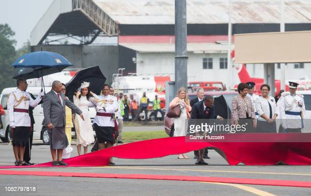 The red carpet blows up as Meghan Duchess of Sussex arrives at Nausori Airport on October 23 2018 in Suva Fiji The Duke and Duchess of Sussex are on...