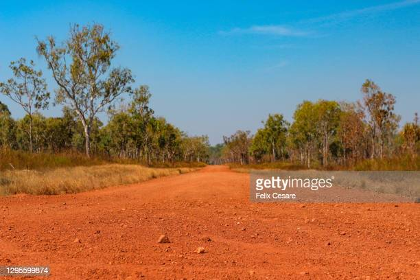the red centre roads in the australian outback. unsealed roads. - エアーズロック ストックフォトと画像