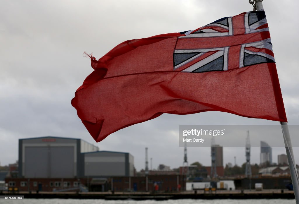 The Red Ensign flies on the harbour ferry as it passes in front of the BAE systems yard at the HM Naval Base in Portsmouth dockyard following the announcement that the company will be cutting jobs on November 6, 2013 in Portsmouth, England. The cuts are being made following a decline in orders, with 1775 jobs going between the yards in Scotland and England and the end of shipbuilding altogether at the Portsmouth yard.