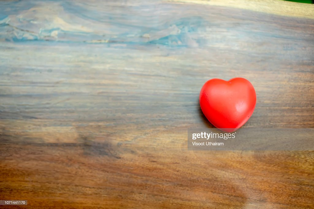 The red heart is placed on the left side of the wood table : Stock Photo