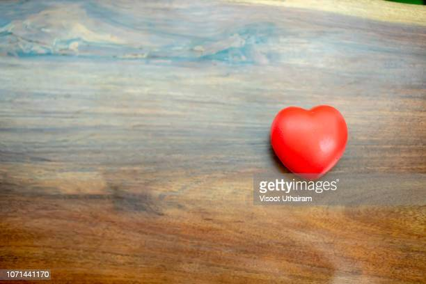 The red heart is placed on the left side of the wood table