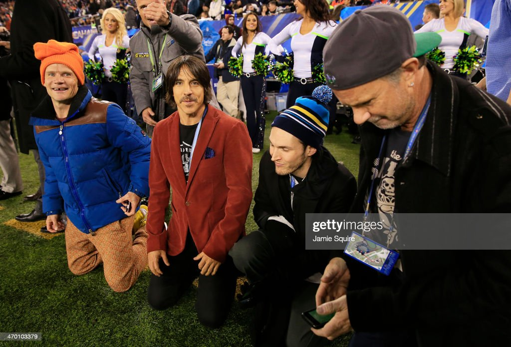 The Red Hot Chili Peppers watch Super Bowl XLVIII between the Denver Broncos and the Seattle Seahawks from the sidelines at MetLife Stadium on February 2, 2014 in East Rutherford, New Jersey.
