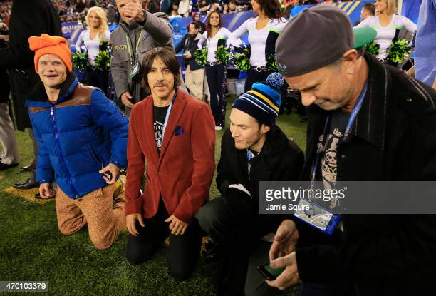 The Red Hot Chili Peppers watch Super Bowl XLVIII between the Denver Broncos and the Seattle Seahawks from the sidelines at MetLife Stadium on...