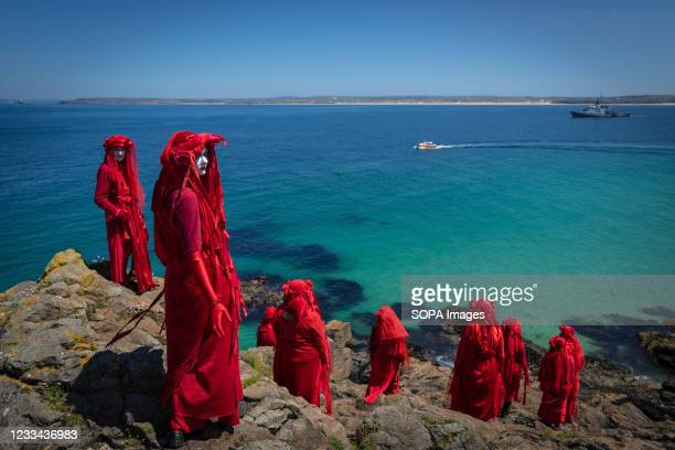The Red Rebel Brigade which is part of the Extinction Rebellion movement pose on St Ives Head. Environmental Protest Groups gather in Cornwall as the...