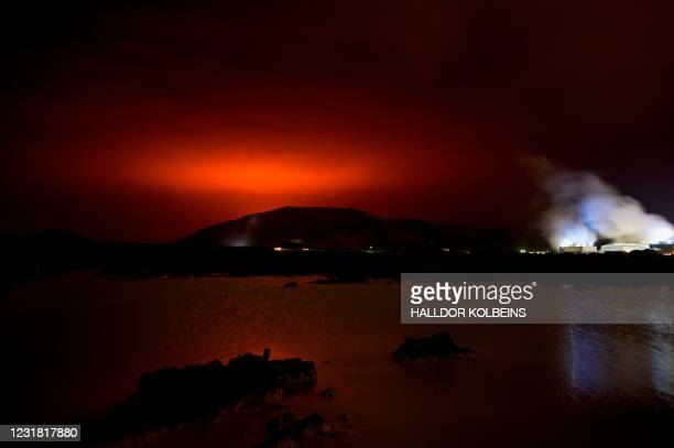 The red shimmer from magma flowing out from the erupting Fagradalsfjall volcano behind the landmark Blue Lagoon, some 45 km west of the Icelandic...