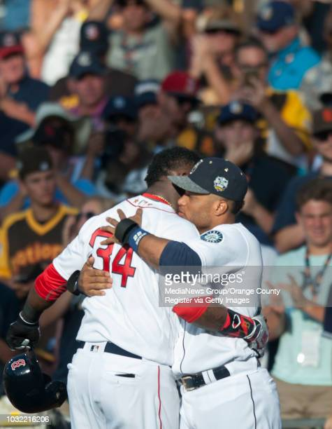 The Red Sox' David Ortiz gets a hug from Robinson Cano as he leaves the game during the American League's 42 victory over the National League during...