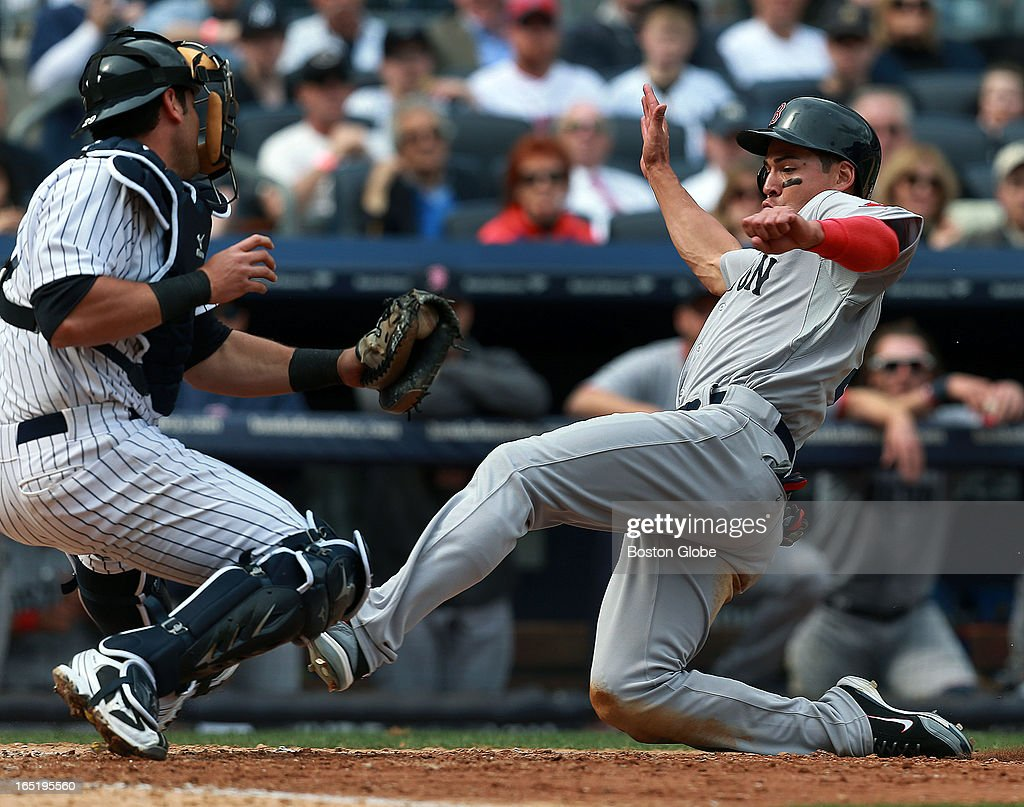 The Red Sox Jacoby Ellsbury is out at the plate, tagged by Yankees catcher Francisco Cervelli as he tried to score from third on a sixth inning ground ball by teammate Dustin Pedroia, not pictured. The Boston Red Sox play the New York Yankees at Yankee Stadium during Opening Day of the 2013 MLB season.